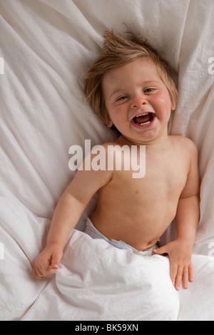 Heureux enfant portant sur le lit Banque D'Images