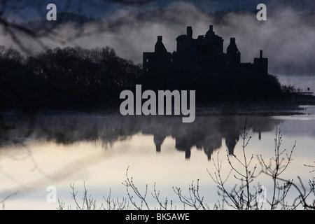 Kilchurn Castle sur les rives du Loch Awe, Ecosse, enveloppée de brouillard tôt le matin