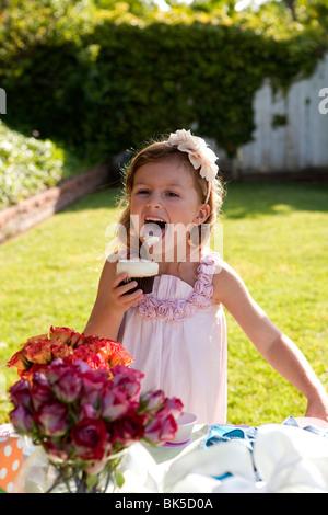 Glaçage cupcake Girl licking off Banque D'Images