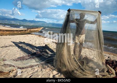 Un pêcheur tend ses filets sur la plage des cocotiers aussi connu sous le nom de Saga Plage, le lac Tanganyika, Banque D'Images