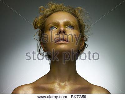 Jeune femme couverte d'or composent Banque D'Images