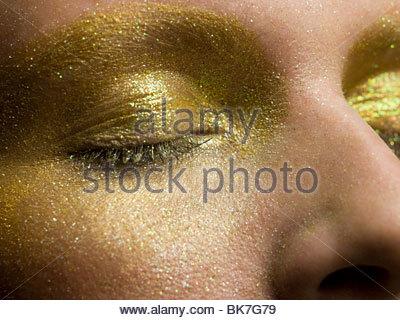 Les yeux couverts de sexe féminin dans l'or forment Banque D'Images