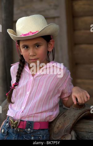 Un mignon 7-9 ans mixed race (caucasienne)/asiatique fille dans un chandail rose, portant un chapeau avec cheveux dans une tresse. (Publié)