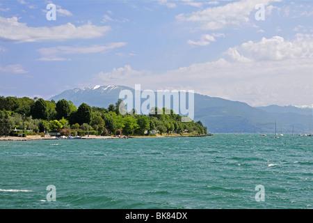 Lac de Garde sur un matin de printemps avec des vagues agitées et une vue lointaine du Monte Baldo avec de la neige Banque D'Images