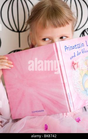 Fille dans sa chambre tenant un livre Banque D'Images