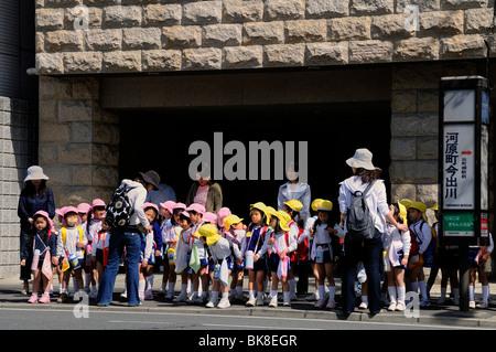 Les enfants, filles et garçons jaune avec rose avec Caps, en attente dans le centre-ville pour le bus, Kyoto, Japon, Asie