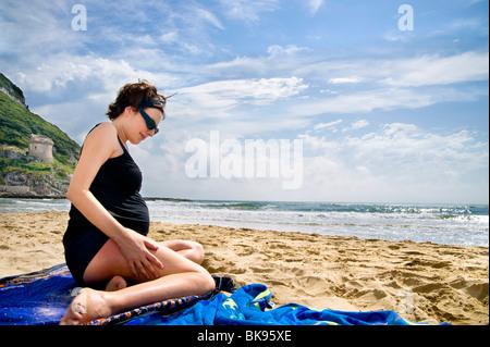 Femme enceinte de s'asseoir sur la plage par la mer Banque D'Images