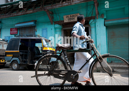 Homme marchant local passé magasin-entrepôt, près du front de mer, fort Cochin, Kerala, Inde Banque D'Images