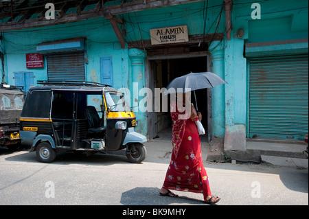 Femme marche local passé magasin-entrepôt, près du front de mer, fort Cochin, Kerala, Inde Banque D'Images