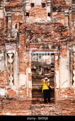 Wat Chaiwatthanaram temple bouddhiste d'Ayutthaya, Thaïlande, avec femme visiteur photographier les ruines. Banque D'Images
