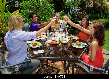 Amis à l'arrière-cour d'un bar-b-que à hawaii L'éducation de leurs verres dans un toast Banque D'Images