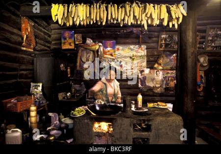 Ze um Latso prépare le déjeuner à la maison au milieu de la pendaison des cors et des affiches et des photos du Banque D'Images