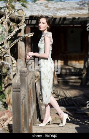 Une belle jeune femme caucasienne est parmi certains bois demeure d'une vieille maison. Elle porte une robe vert pastel.