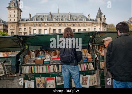 La navigation sur les touristes, les vieux livres en vente à l'extérieur du marché de trottoir, Paris, France, Seine Banque D'Images
