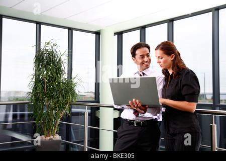 Asian male et femelle blanche des employés de bureau en bureau pour ordinateur portable à l'aide de l'environnement contemporain.