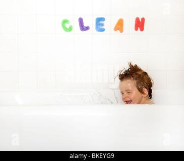 Garçon s'éclabousser dans une baignoire Banque D'Images