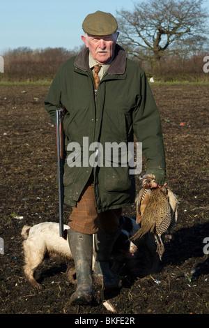 Un homme chasse transportant son arme, faisans et perdrix de marcher à travers les champs Banque D'Images