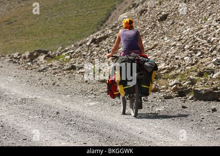 Cycliste féminine sur une route de montagne, le Kirghizistan Banque D'Images