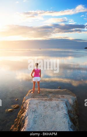 Girl à la fin de la jetée à la recherche dans le coucher du soleil; le sud de Batangas, Matabungkay Luzon, Philippines Banque D'Images
