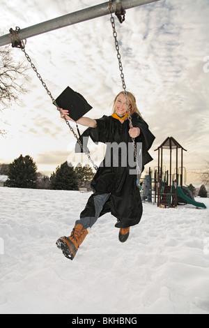 Happy blonde woman in graduation cap une toge swinging sur aire de swing Banque D'Images