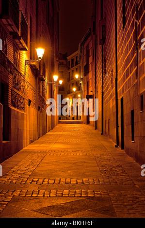 Ruelle éclairée par des lampadaires la nuit, Madrid, Espagne Banque D'Images