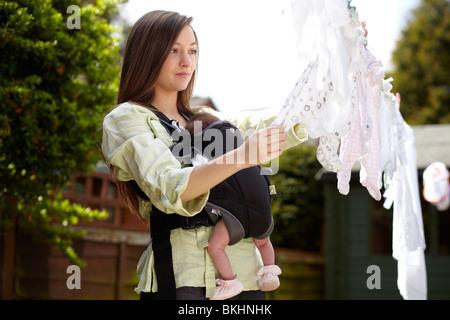 Femme avec bébé en tenant en ligne de lavage Banque D'Images