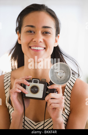 Mixed Race woman holding old-fashioned camera Banque D'Images