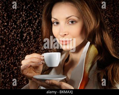 Belle Jeune femme tenant une tasse de café avec café en grains derrière elle en arrière-plan Banque D'Images