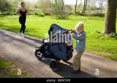 Bébé poussé dans un landau / poussette qui est poussé par un petit garçon, âgé de cinq ans.