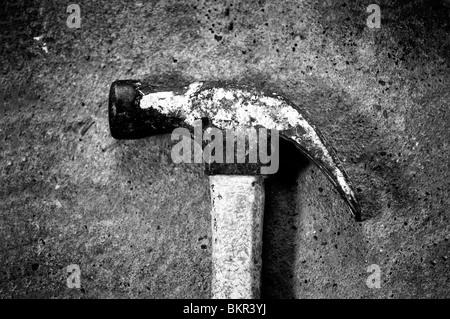 Un marteau utilisé bien photographié sur un sol en béton. Banque D'Images