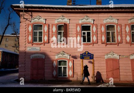 La Russie, la Sibérie, Irkoutsk; une fille qui marche par une maison traditionnelle en bois. Banque D'Images