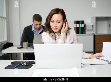 Woman looking at laptop, collègue travaillant en arrière-plan Banque D'Images