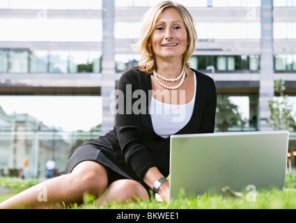 Businesswoman sitting in park with laptop Banque D'Images