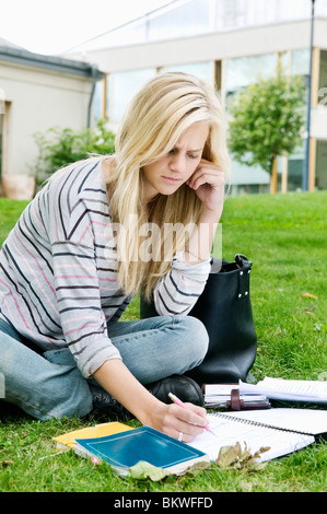 Femme assise à l'extérieur de l'écriture dans le bloc-notes Banque D'Images