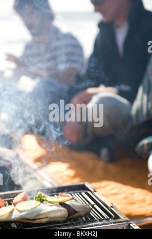 Groupe d'amis assis autour d'un barbecue sur la plage Banque D'Images