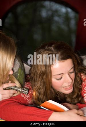 Deux adolescentes se trouvant dans une tente de lire un livre aux flambeaux