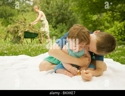 Jeune garçon assis dans un jardin en embrassant une embrasser son petit frère Banque D'Images
