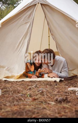 Jeune couple couché dans une tente, entrée privée