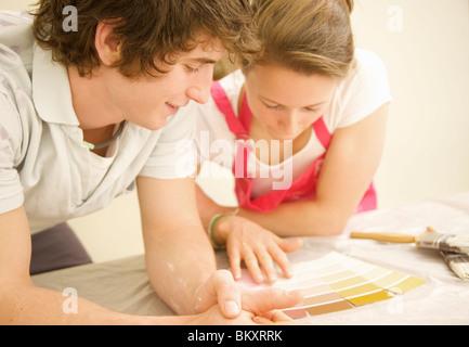 Close up of a smiling couple penchées sur un tableau à la peinture en couleurs du nuancier Banque D'Images