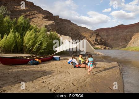 Deux jeunes filles jouant près de leur mère tout en camping sur la Rivière San Juan, Mexican Hat, Utah. Banque D'Images