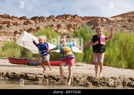 Trois jeunes filles dans les gilets de sauter dans la rivière San Juan, Mexican Hat, Utah. Banque D'Images