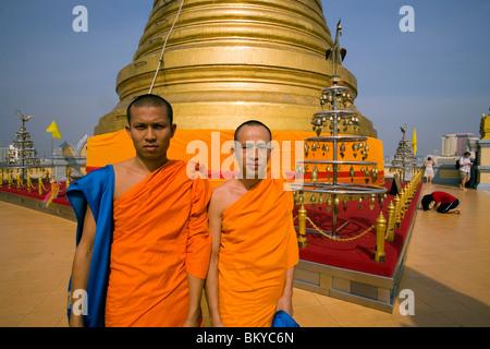 Deux moines en face du chedi doré, abritait une relique de Bouddha du Wat Saket sur le Mont d'or, femme qui prie Banque D'Images