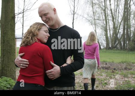 Jeune femme MARCHE LOIN DE COUPLE HUGGING EXTÉRIEUR. Banque D'Images