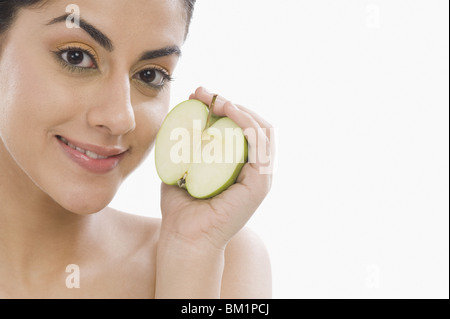 Portrait de femme tenant une moitié de pomme verte Banque D'Images