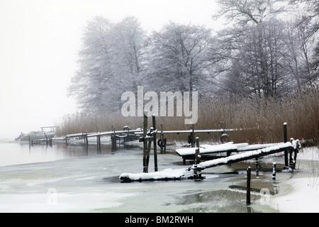 Ancienne jetée jetées amarrage bateau tôt le matin, le brouillard et le gel des terres sur la neige hiver profonde Banque D'Images