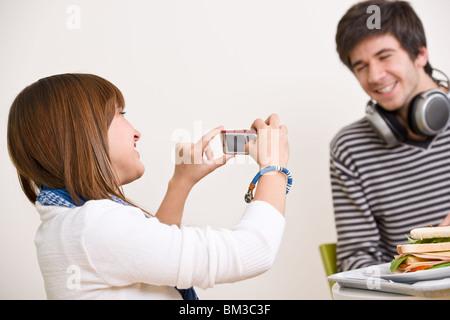 Étudiants - teenage couple taking photo with mobile pendant la pause déjeuner dans la cafétéria Banque D'Images