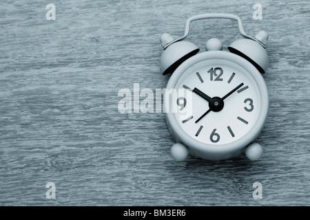 Petit mignon réveil photographie monochrome sur la table en bois Banque D'Images