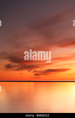 Rouge feu nuages dériver dans un ciel crépusculaire juste après le coucher du soleil à Ludington, Michigan, comté Banque D'Images