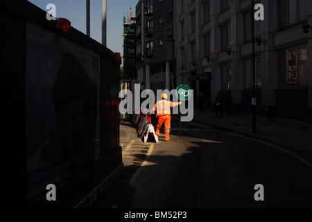 Le trafic d'un prévôt vêtu d'un costume haut-vis se trouve sur un chemin public pour guider la circulation en sens Banque D'Images
