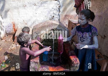 Girl le dépôt d'une bouteille d'eau et de colorants. Festival de Holi. Varanasi. L'Inde Banque D'Images